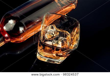 Top Of View Of Glass Of Whiskey Near Bottle On Black Table With Reflection