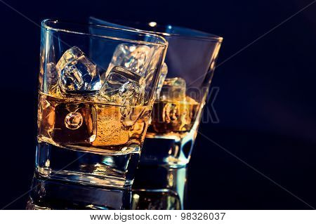 Two Glasses Of Whiskey With Ice Cubes On Black Background With Light Tint Blue