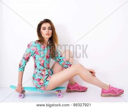 Fashion hipster girl in colorful dress with skateboard having fun . flirting against the white wall