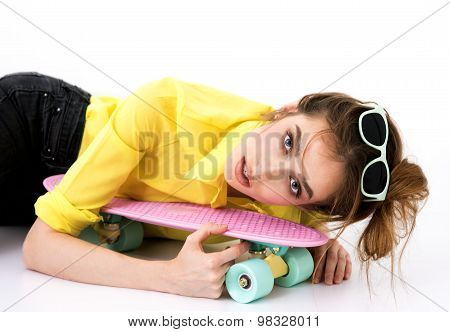 Fashion hipster girl in yellow shirt in sunglasses with skateboard flirting against the white wall.