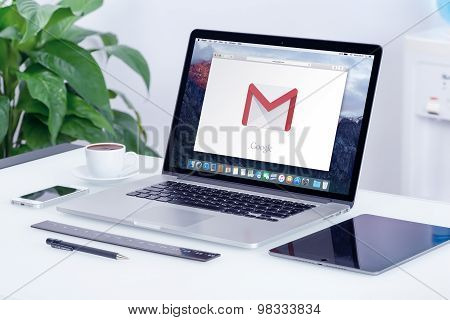 Google Gmail logo on Apple MacBook Pro display that is on office desk in modern office work place