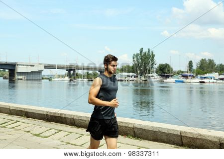 Young man jogging near river