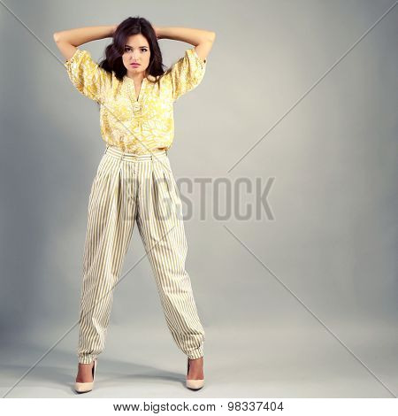 Young woman dressed in retro style on grey background