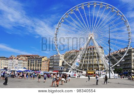 MARSEILLE, FRANCE - MAY 17: Sunday ambiance and Ferris wheel at the Old Port on May 17, 2015 in Marseille, France. It is a busy port, used as a marina and as a terminal for boat trips