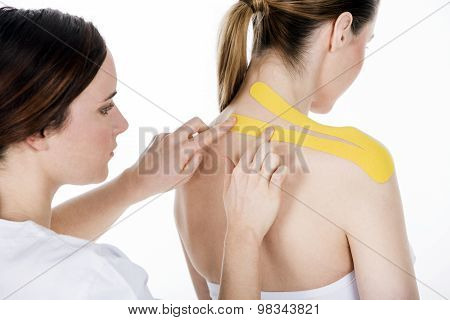physioterapist getting tapes on the trapezius