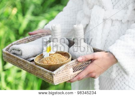 Woman in bathrobe holding wicker tray with spa products on river