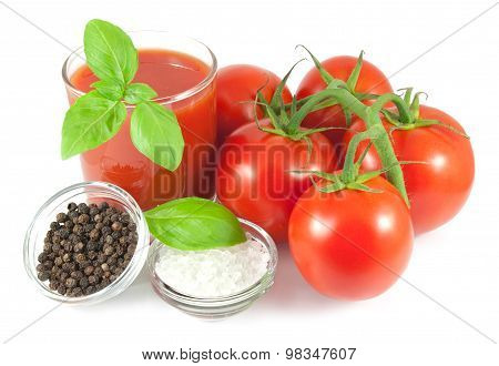 Bunch of fresh tomatoes with basil leaves, glass of tomato juice and bowls with pepper and salt