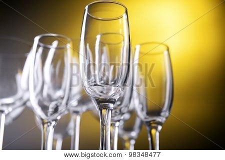 Empty champagne glasses on yellow background