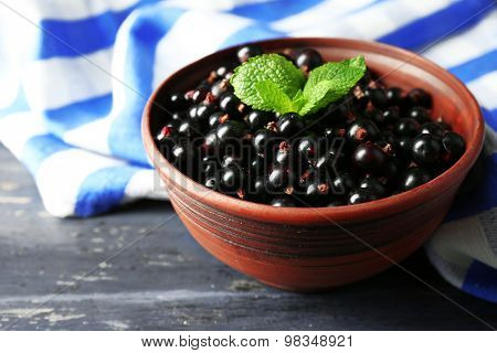 Ripe blackcurrant in bowl on wooden background