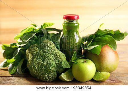 Green healthy juice with fruits and vegetables on wooden background