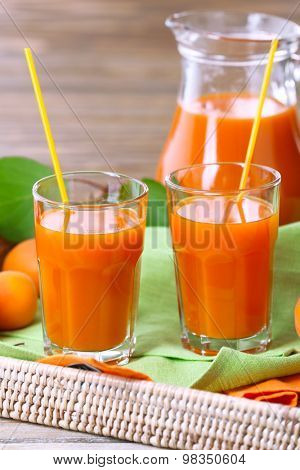 Glasses of apricots juice in wicker tray on wooden background