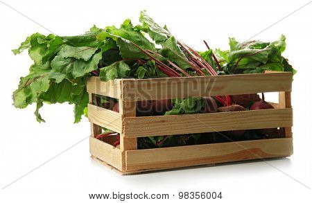 Young beets with leaves in crate isolated on white