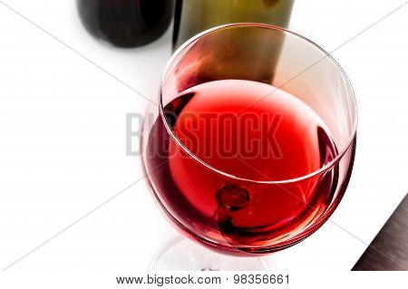 Top Of View Of Red Wine Glass Near Wine Bottles