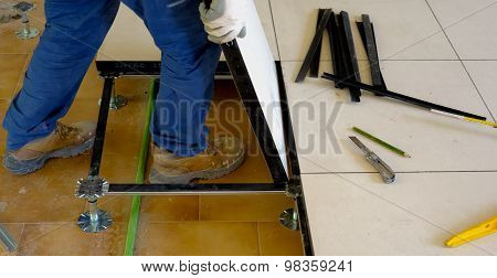 worker carries a floating floor on steel feet resting