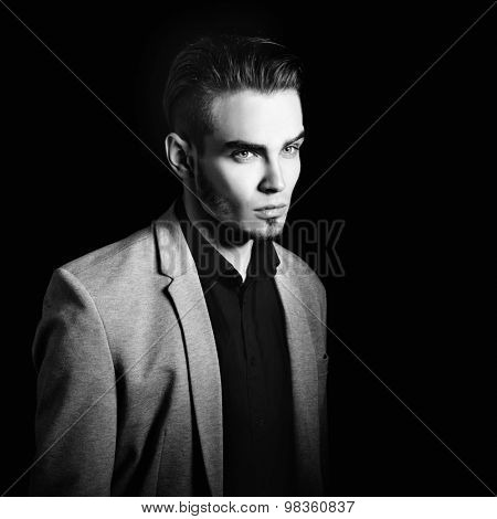 Black and white portrait of attractive mysterious young man over black background.