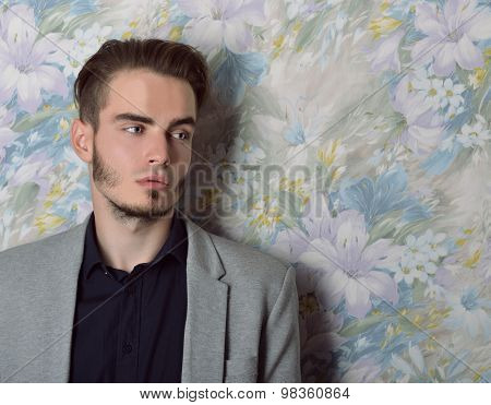 Portrait of attractive young mysterious man lokking right at copy space, over floral background. Image toned.