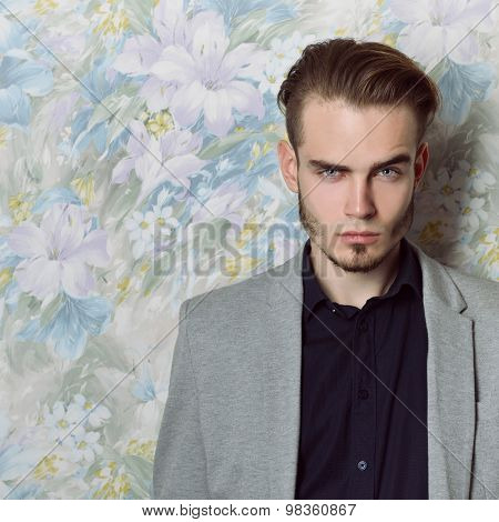 Portrait of attractive young mysterious man looking at camera, over floral background.