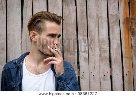 Young handsome man smoking outdoor against grunge obsolete fence