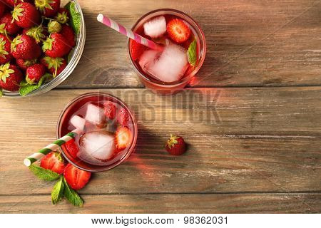 Glasses of strawberry juice with berries on table close up