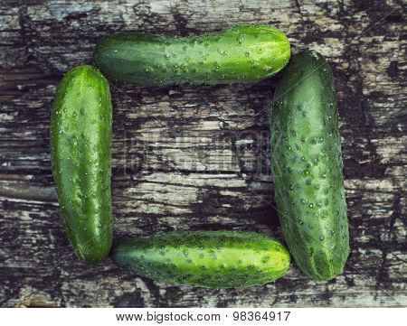 wood background with fresh cucumbers, space in the middle for text