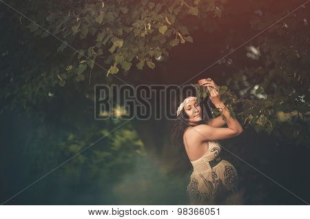 Romantic, beautiful pregnant woman outside in the park among trees  and greenery like a fairytale