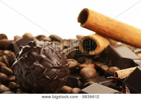truffle in front of cinnamon sticks and coffee beans on a chocolate bar