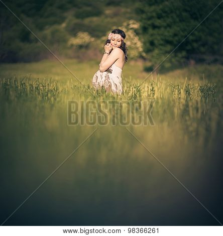Romantic pregnant woman outside, in the field and among greenery like a fairytale.