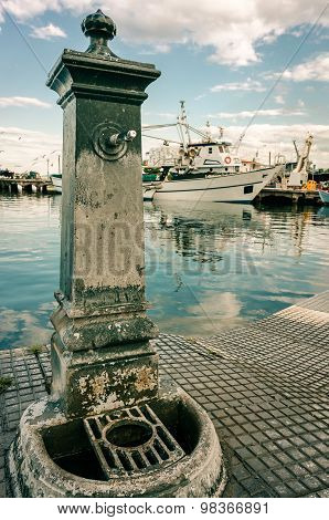 Old Faucet In Lagoon Harbor With Ships And Green Water Background