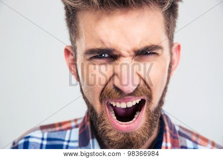 Portrait of a young man screaming isolated on a white background. Looking at camera