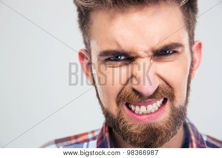 Closeup portrait of angry man looking at camera isolated on a white background