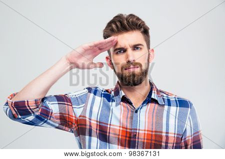 Portrait of a young man saluting isolated on a white background. Looking at camera