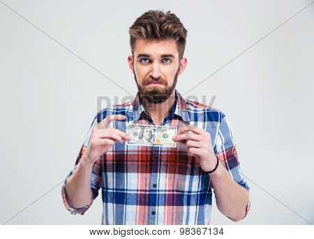 Portrait of a casual man holding bill of USA dollar isolated on a white background and looking at camera