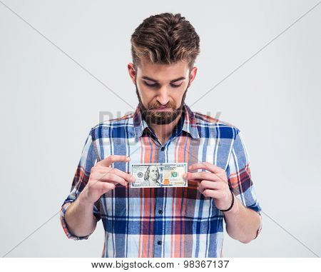 Portrait of a young man holding bill of USA dollar isolated on a white background