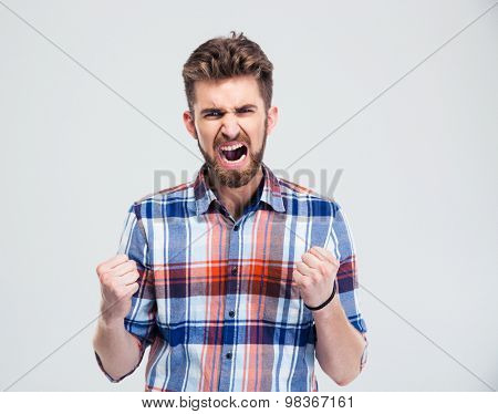 Angry man shouting isolated on a white background. Looking at camera