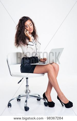 Happy businesswoman using laptop and talking on the phone while sitting on the office chair isolated on a white background
