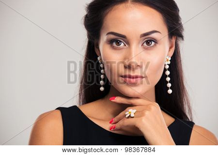 Jewerly concept. Closeup portrait of a pretty female model posing isolated on a white background. Looking at camera