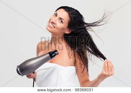 Smiling cute woman in towel drying her hair isolated on a white background