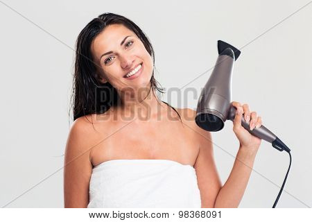 Smiling cute woman in towel holding hairdryer isolated on a white background. Looking at camera