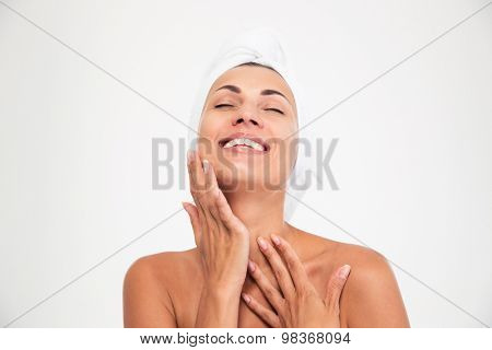 Spa concept. Portrait of a happy woman with towel on head touching her face isolated on a white background. Looking at camera