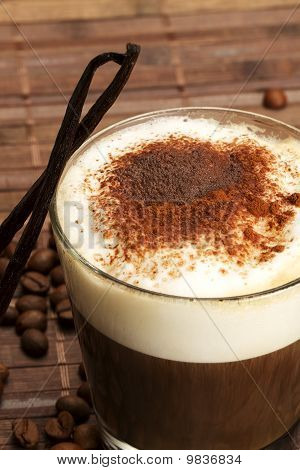 coffee with milk froth, cocoa powder and standing vanilla beans