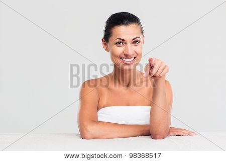 Portrait of a happy woman in towel sitting at the table and pointing finger at camera isolated on a white background