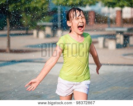Hot summer in the city - girl is ruining through fountains
