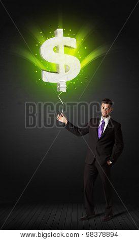 Businessman holding a shining, green dollar sign balloon