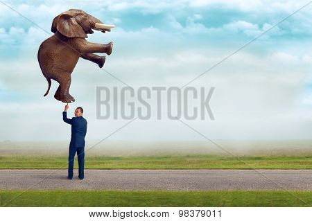 Businessman Holding An Elephant With One Finger
