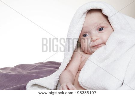A funny baby on towel sit on the bed
