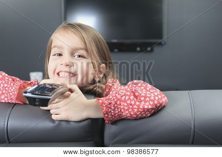 cute little girl with remote control in front of TV.