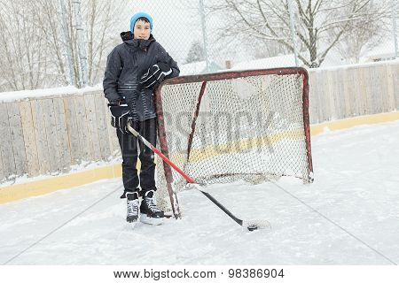 teenager playing hockey outside on a ice rink.