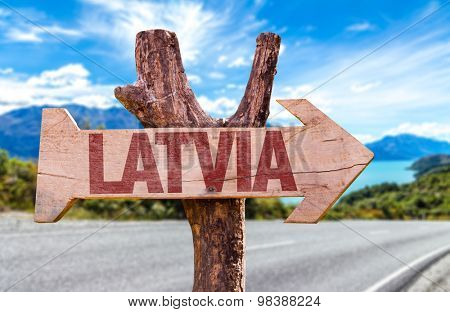 Latvia wooden sign with road background