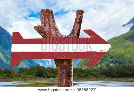 Latvia Flag wooden sign with landscape background
