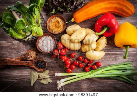 Raw vegetables with spices on wooden table